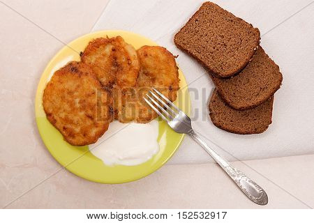 Potato Pancakes With Meat And Sour Cream On Green Plate With Rye Black Bread Metal Fork In Belarusia