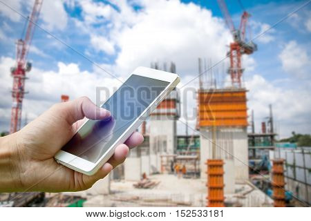 Hand holding smartphone on blurred construction site workers with cloud and blue sky