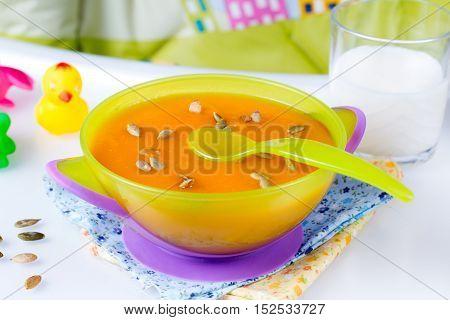 Pumpkin cream soup with pumpkin seeds and a glass of milk