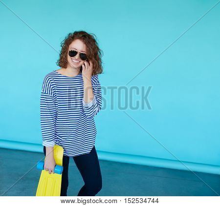 beautiful young brunette model girl in casual hipster clothes with skateboard behind blue colorful background