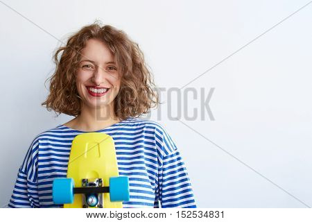 Fashion hipster girl in a striped shirt with a colorful skateboard posing against the white wall with copyspace. Happy young woman with yellow longboard