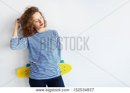 Portrait of a hipster girl holding a skateboard isolated on white background. Young woman wearing casual urban clothes posing with longboard in studio over white wall with copy space