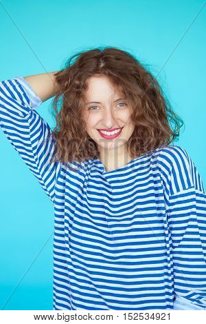Summer fashion girl with curly hairstyle wearing nautical style clothes. Marine concept of young female in striped shirt isolated on bright blue background.