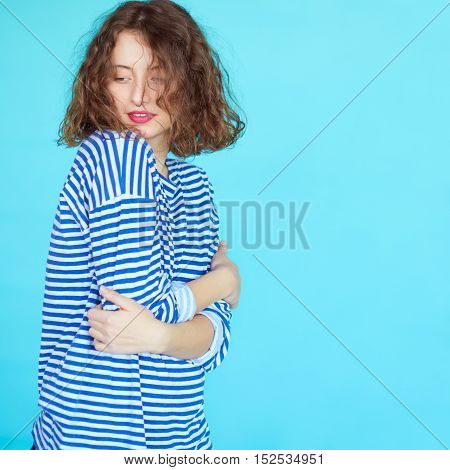 Portrait of a beautiful graceful curly woman in casual clothes with red lips on blue background. Beauty, fashion concept.
