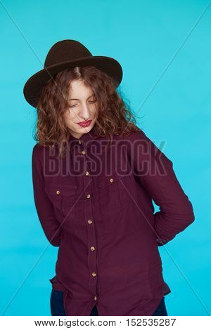 Hipster fashion brunette girl with curly hair and hat. Young woman posing in studio isolated on vivid blue background.