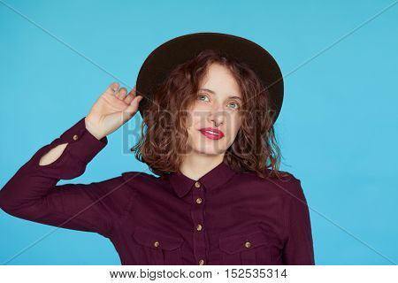 Fashion portrait of sensual stylish woman with curly hair and hat on a blue background.