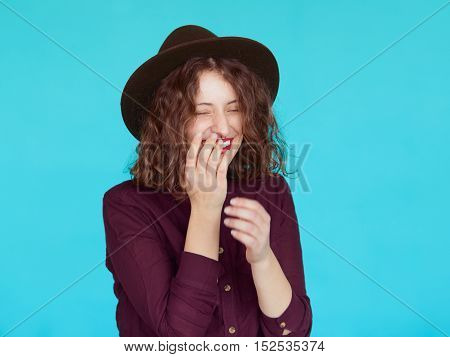 Laughing young woman wearing violet shirt and stylish hat. Happy hipster girl with eyes closed covering her mouth