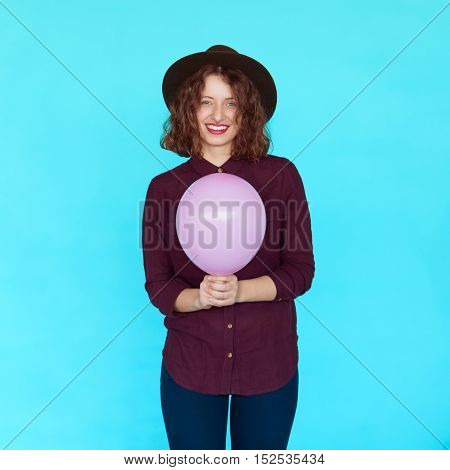 Trendy brunette girl wearing stylish hat, holding a pink balloon and smiling against blue background, isolated. Casual lifestyle with beautiful hipster girl