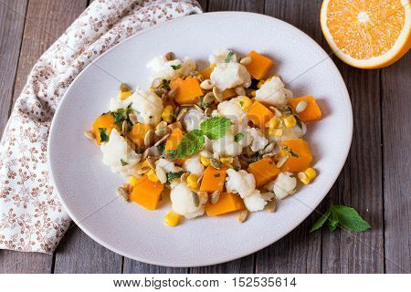 Roasted pumpkin salad with cauliflower in a plate on a wooden background
