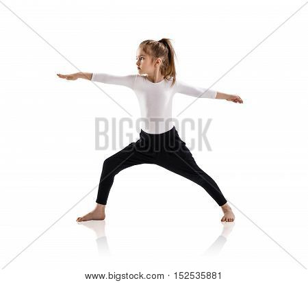 Little cute girl doing yoga exercises isolated over white