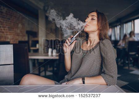 beautiful brunette smoke electronic cigarette in public places