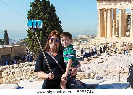 Athens, Greece - October 14, 2016: Lady and boy making selfie near temple ruins in Acropolis, Athens