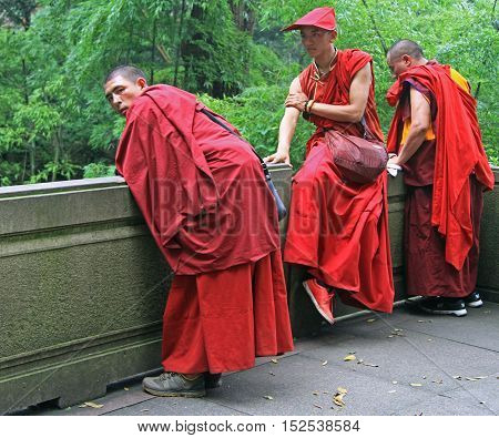 Buddhist Monks In Traditional Clothes Are Resting Outdoor