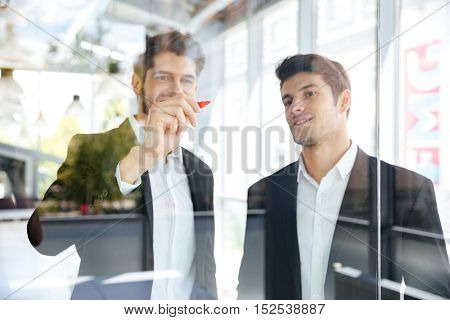 Two happy successful young businessmen writing on glass board in office