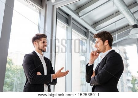 Two handsome young businessmen smiling and talking in office
