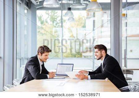 Two happy young businessmen working together using laptop on business meeting in office