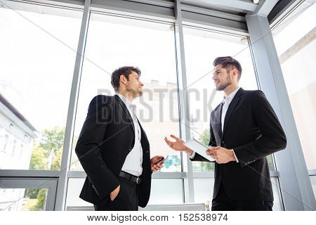Two handsome young businessmen with tablet and mobile phone talking in office