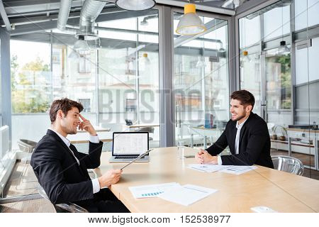 Two happy young businessmen sitting and working together on business meeting