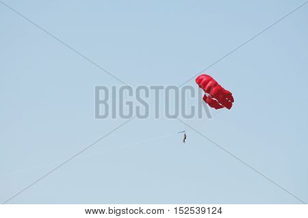 Red Parachute Parasailing and Clear Blue Sky