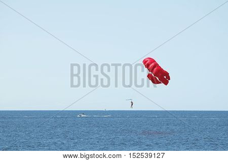 Red Parachute Parasailing Sea and Clear Blue Sky