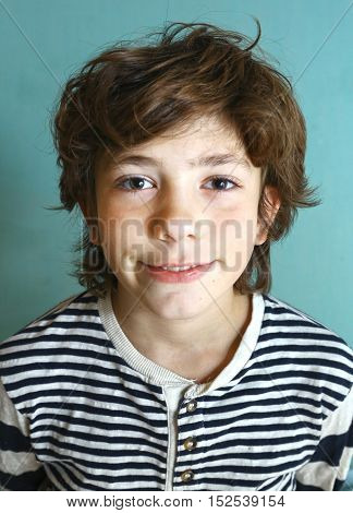 preteen happy boy close up photo on blue background