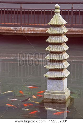 miniature of traditional chinese pagoda in pond with fishes park of Hangzhou China