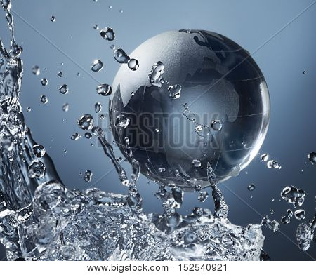 glass globe planet in drop water splash on blue background
