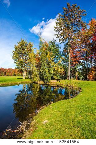 Concept of recreational tourism. Shining day in French Canada. Autumn foliage reflected in clear water of the pond. Adorable oval pond in the beautiful park