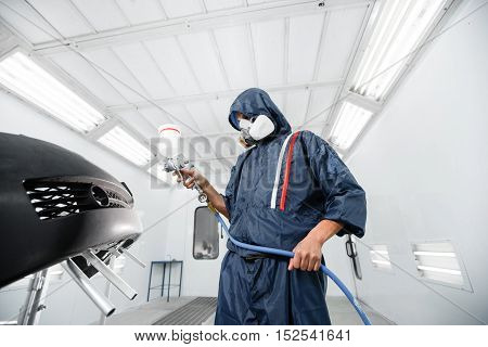 worker painting a car black blank parts in special garage, wearing costume and protective gear.