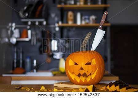 Head jack lantern pumpkin with a table knife in a modern kitchen.