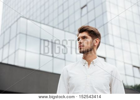 Portrait of handsome young businessman standing near business center