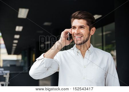 Portrait of happy handsome young businessman talking on mobile phone near business center