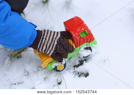 Part of the image of a small child who is sitting in the first snow and playing with colorful toy car.