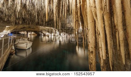 Wide angle long exposure of touristic cave with lake, stalactites and stalagmites, boat