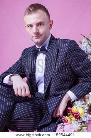 Portrait of bridegroom sitting on chair with  artificial flowers winking against pink background