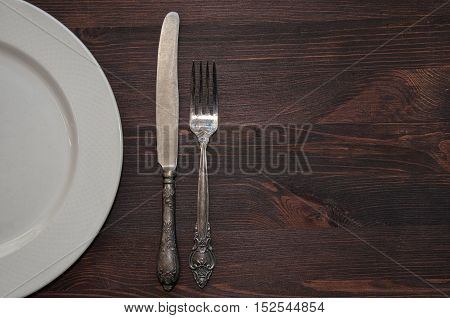 Half empty white plates vintage knife and fork on brown table top view