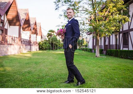 Side view of smiling groom holding bouquet on lawn