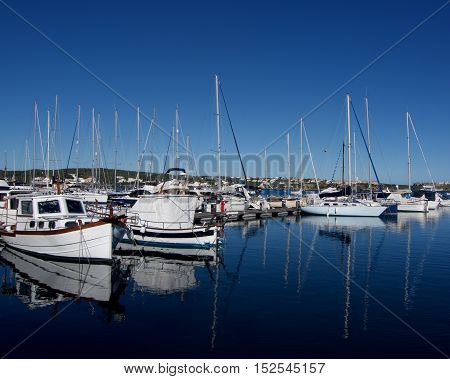 Various Anchor Yachts with Reflection in Surface of Sea in Marina of Mahon Menorca Spain