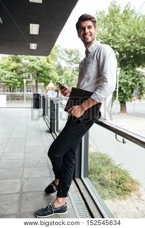 Happy young businessman with folder standing and using smartphone outdoors