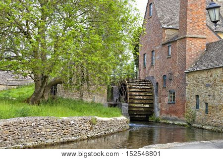Old water mill with undershot waterwheel and red brick chimney on the edge of traditional english village