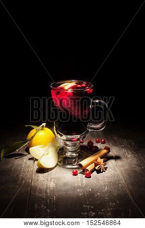 mulled wine with apple and mandarin on a black background vertically