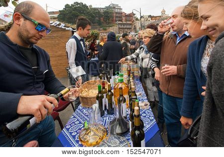 TBILISI, GEORGIA - OCT 16, 2016: Tasting class with crowd of people drinking wine with bartender at festival Tbilisoba on October 16, 2016. Tbilisoba is traditional festival in capital of Georgia from 1979