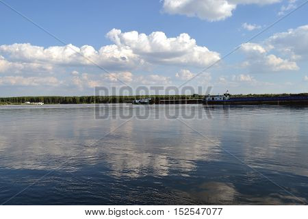 Afternoon on the Danube with white clouds, blue skies and barges carrying various goods.