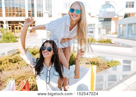 Two smiling happy women having fun while sitting on the bench after shopping