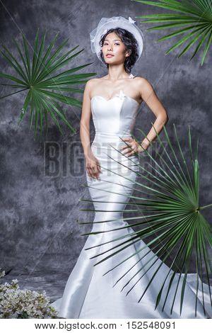 Portrait of elegant bride standing against grey wall