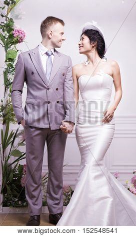 Portrait of beautiful bride standing with bridegroom against wall