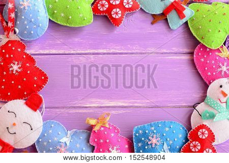 Colorful Christmas decorations. Cute felt Christmas trees, mittens, snowmen, hearts, stars on lilac wooden background with empty place for text. Merry Christmas design. Happy new year design. Top view