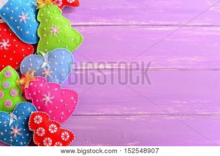 Colorful Christmas background. Cute felt Christmas trees, mittens, hearts, stars on lilac wooden background with empty copy space for text. Winter holiday background. Top view