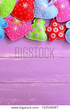 Colorful Christmas toys. Felt Christmas trees, mittens, hearts, stars on lilac wooden table with empty place for text. Merry Christmas background. Happy new year background. Top view