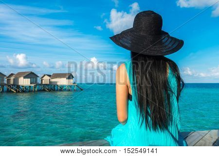 Portrait of happy young woman at beautiful water villa at Maldives island. Travel and Vacation. Outdoor shot
